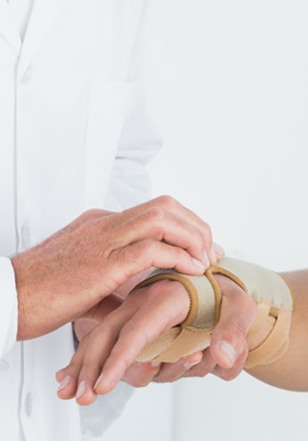 Doctor putting patient's hand in brace
