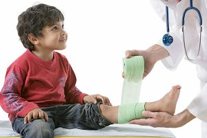 pediatric doctor helping child with leg injury